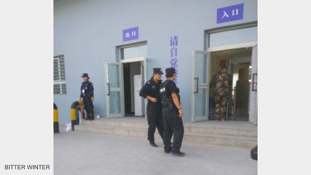 Police patrol and stand guard outside the re-education camp