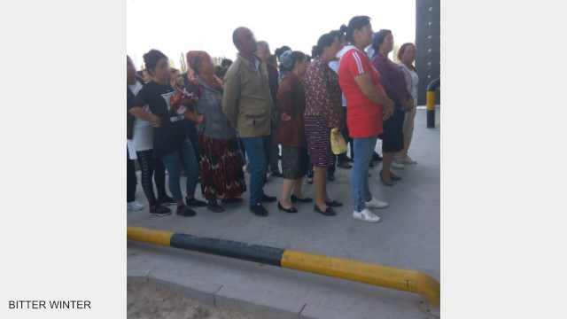 The detainees' family members who are attending the public trial meeting line up outside the re-education camp, waiting to be summoned